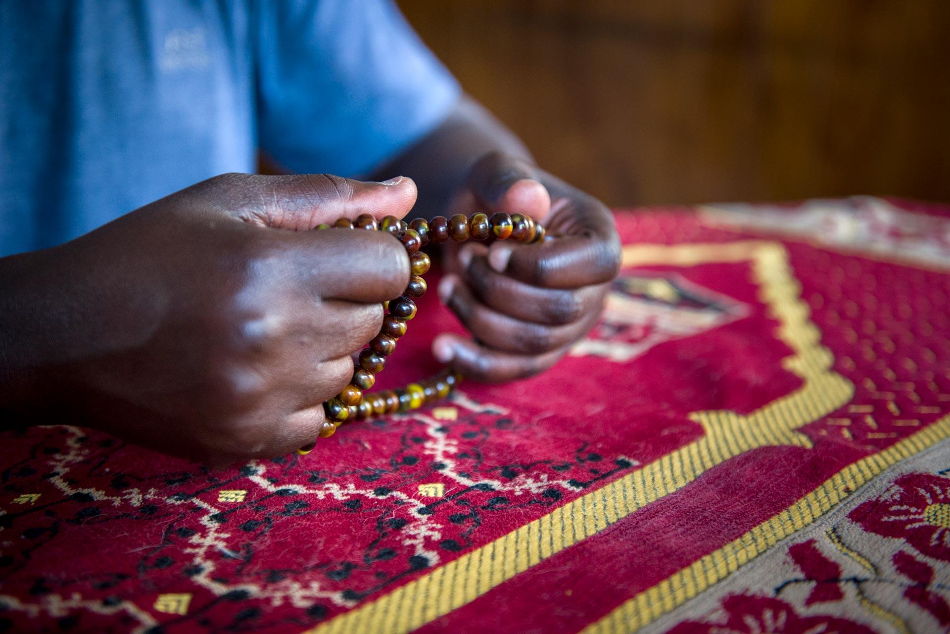 Nar sostiene un rosario de cuentas de madera. Fotografía: Pablo Presti / Cosecha Roja