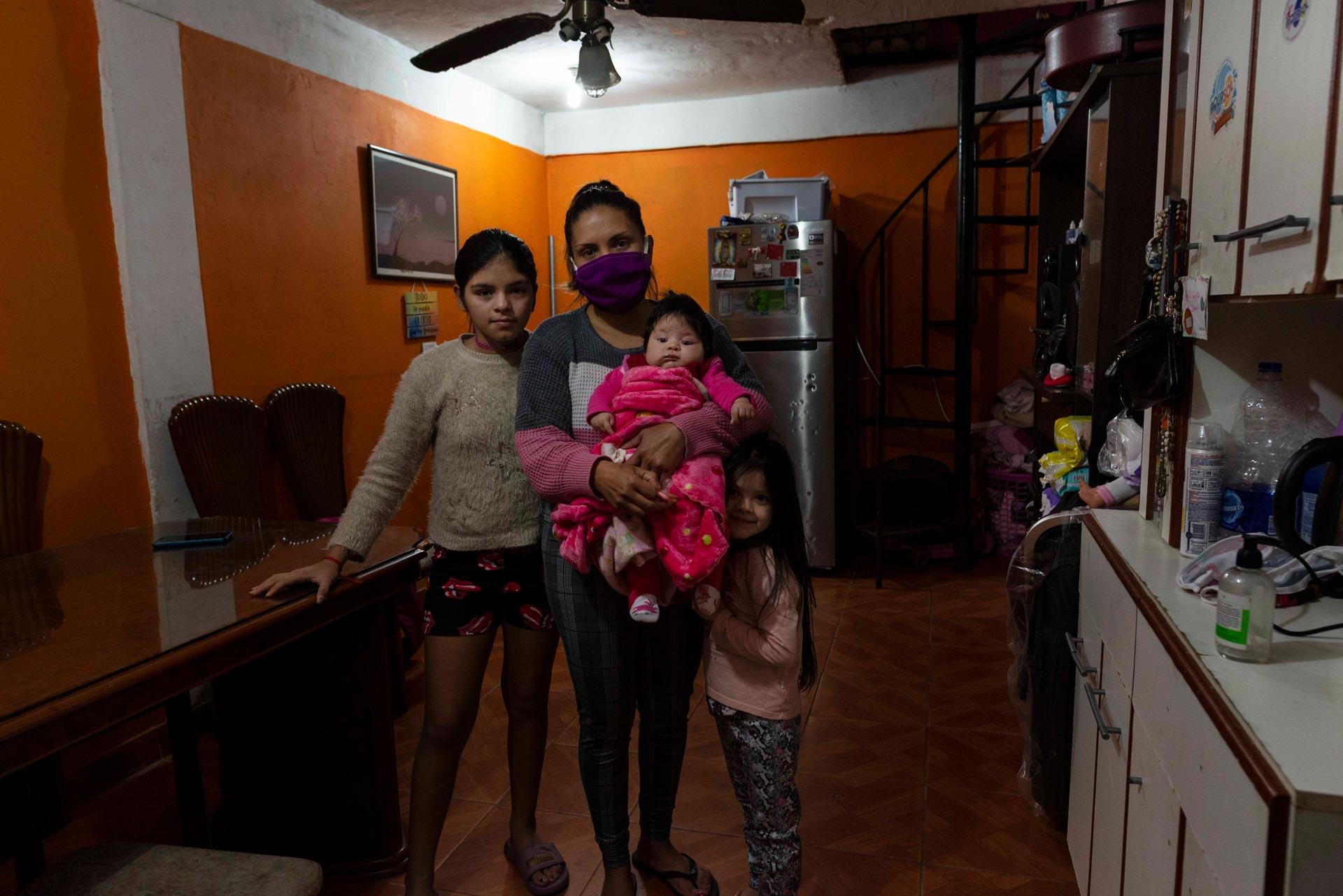 El camión no llega a la casa de Ana que vive con sus tres hijas y su marido. Ambos son vendedores ambulantes. Por la pandemia ella está sin trabajo. Hace 10 días que la familia no tiene agua. Ana (26) posa para esta fotografía con sus hijas Agostina (10), Juana (5) y Lara (3 meses).